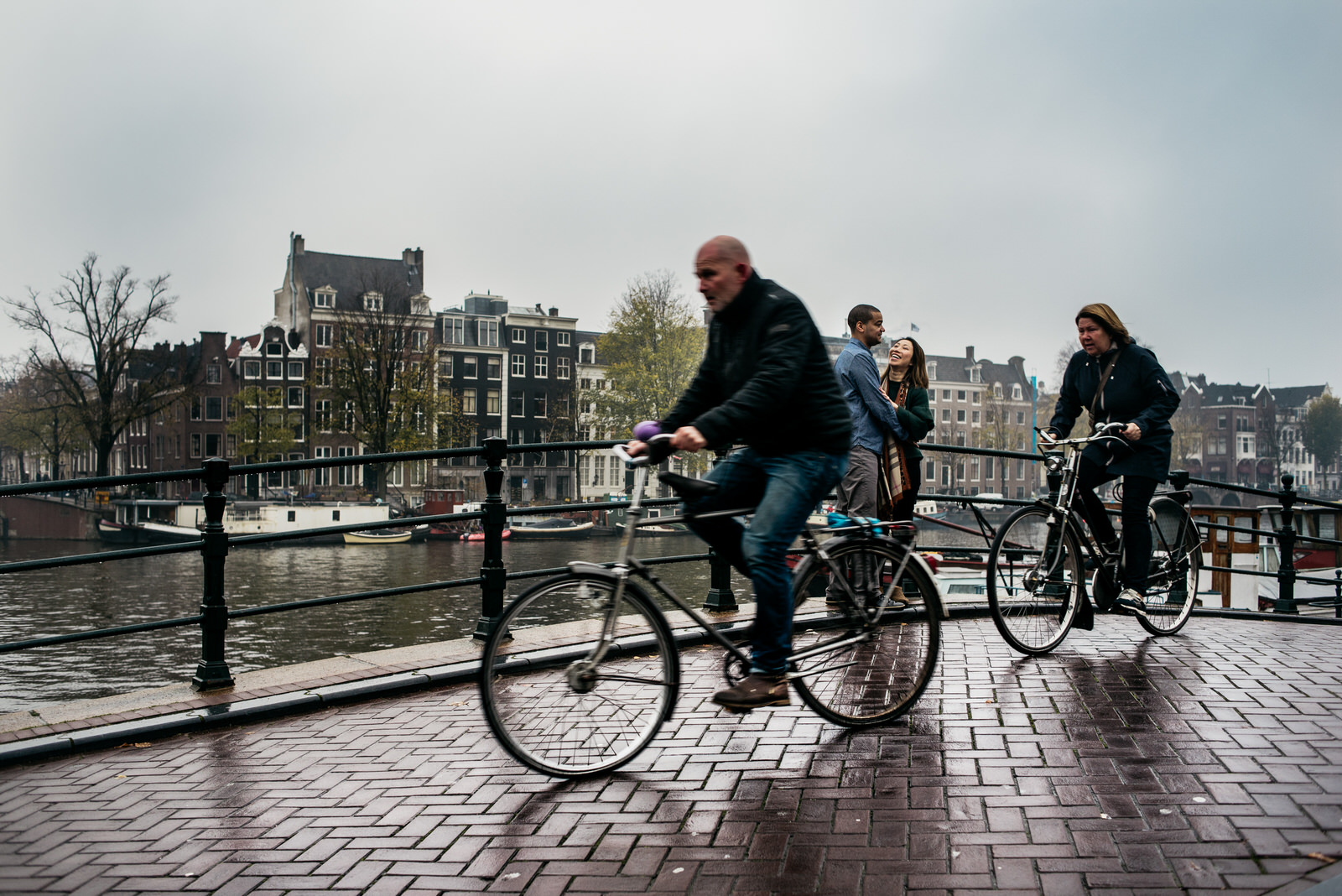 Couple on a bridge in Amsterdam, bikers crossing the bridge during a family shoot in Amsterdam