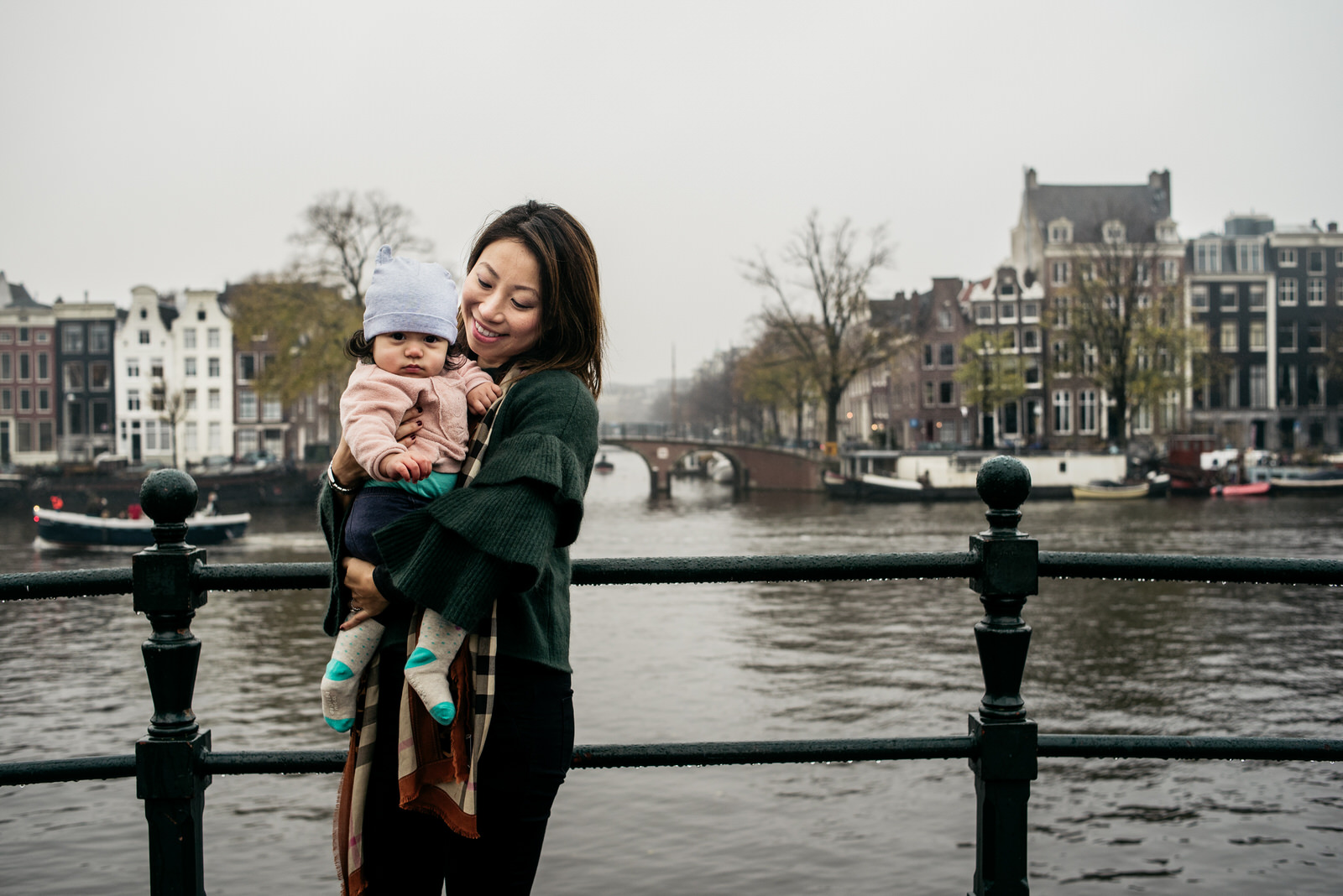 Young mother and her csmall hild on a bridge during a family shoot in Amsterdam
