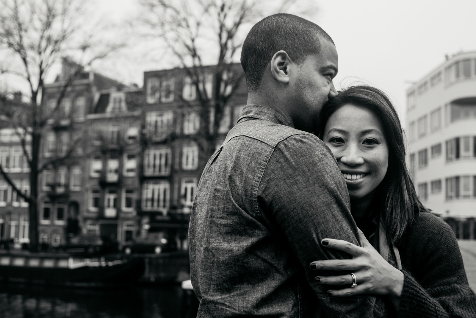 couple taking on a backdrop with buildings in Amsterdam, girl looks into the camera during a family shoot in Amsterdam